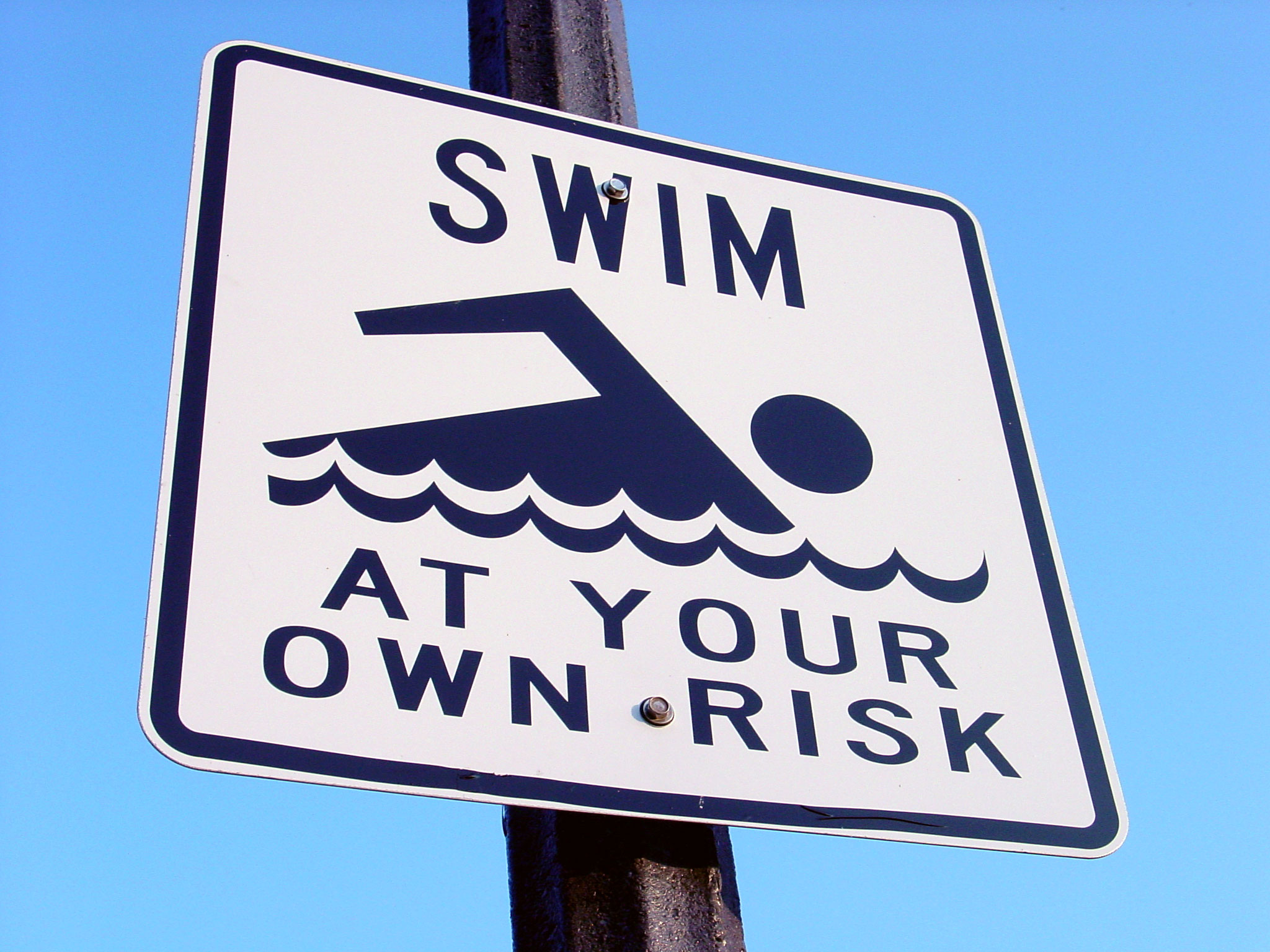 "Skilt med teksten ""Swim at your own risk"""